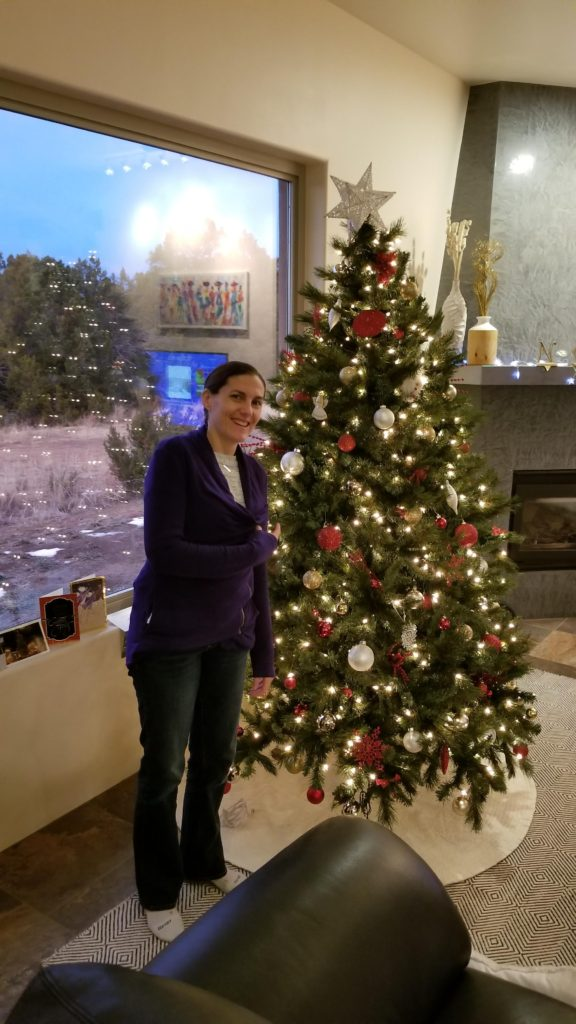 Lis standing by a Christmas Tree