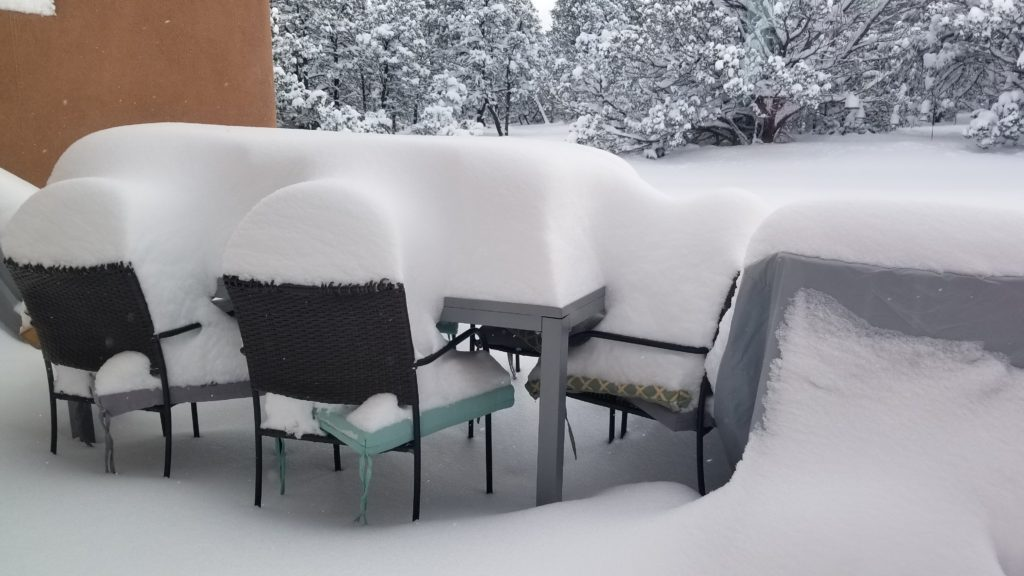 Two feet of snow covered patio furniture.