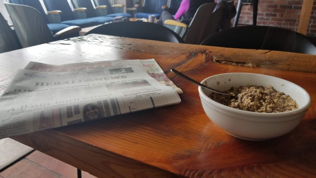 Bowl of oatmeal and a newspaper.