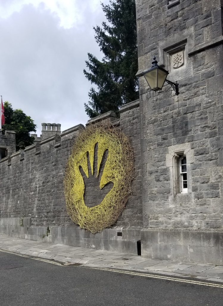 A large art piece on the side of castle walls.