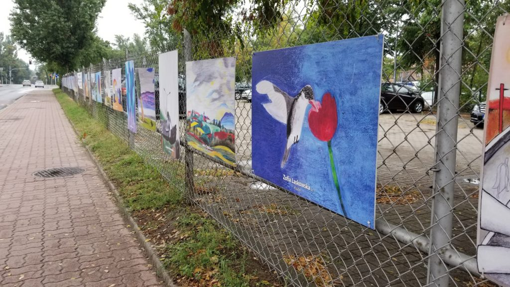Student paintings hung on a fence