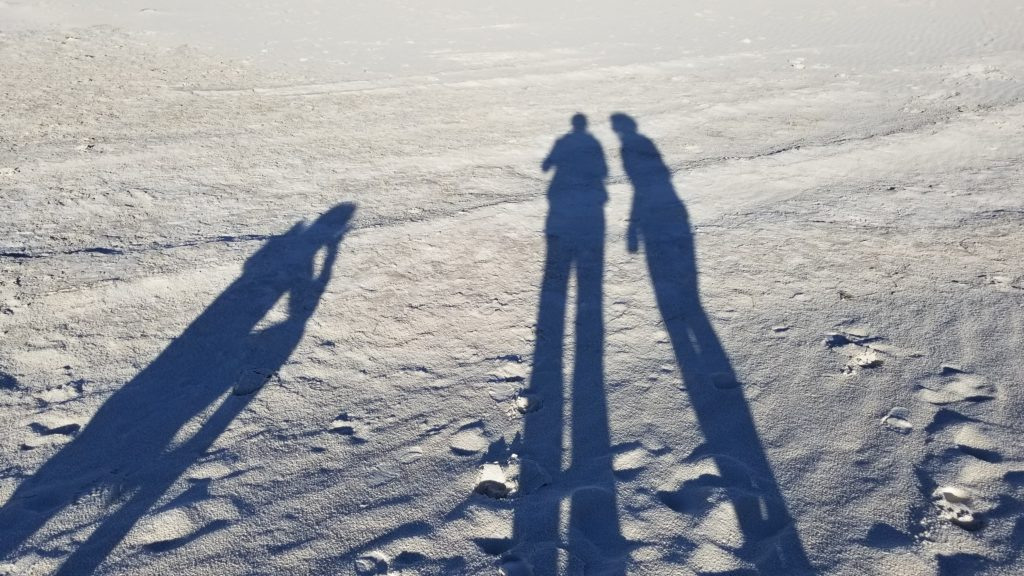 Shadows of three women against the white sands.